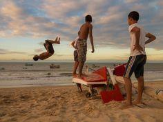 Meninos brincam de dar cambalhotas usando como plataforma jangadas de pescadores na Praia de Maceió, em São Miguel do Gostoso