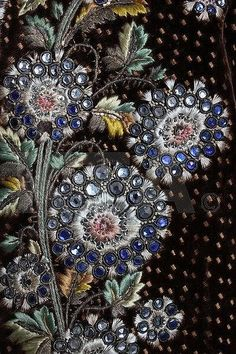 Detail embroidery, 3-piece court suit, France, 1790. Dark brown velvet with magnificently embroidered and irridescent paste studded flowerheads and foliage; waistcoat: ivory silk satin with similar embroidery.