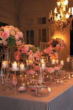 Peach and coral floral arrangements and tall stems of candles and pearls on the dessert table designed by Stoneblossom