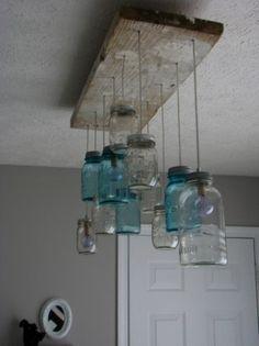 Lamp van een oude plank en (jam) potjes. Technieken; houtbewerking, elektra, schilderen.