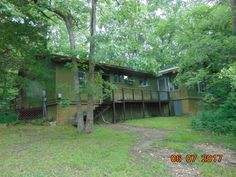 2 bed, 2 bath home secluded in the trees. Nice deck on front of house. Additional room is a very nice sun room. This is a park like setting with more than an acre of ground. All wood floors and all electric in Green Forest AR