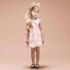 Girls very pretty pink sleeveless dress by<span>Hucklebones London, with the designer's uniqueharlequin pattern. Made from a woven cotton blend jacquard the skirt has wide box pleats at the waist giving a flared, full shape. It has a large white organdy bow on one shoulder and fully lined with a tulle underskirt, fastening with a concealed zip at the back.<br /></span> <ul> <li>48% polyester, 27% cotton, 25% polyamide (woven jacquard feel)</li> <li>Lining: 100% polyamide (silky f...