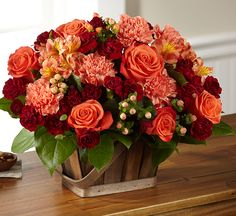 Orange roses, orange carnations, orange Peruvian Lilies, and peach hypericum berries, offset by burgundy mini carnations and lush greens