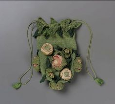 """Rose Bud"" drawstring bag. Italian or French, 1820–60 Green silk knit with appliquéd pink, salmon, ecru roses and yellow-green, green, dark green leaves. Green cord drawstring."