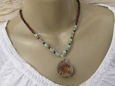 Earthy Ammonite fossil necklace  Ammonite is a fossil that dates back to the age of the dinosaurs. The closest modern relative to the ammonite