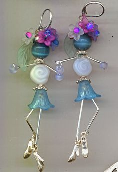 """Flower Dancer"" earrings made with lucite flower beads, coin beads, wire, freshwater pearls and charms."