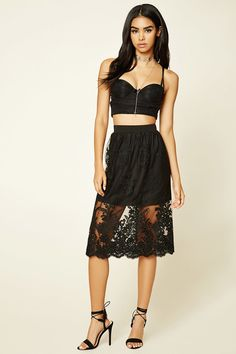 A knit skirt featuring a sheer mesh overlay with crocheted floral appliques, a scalloped hem, mini skirt underlayer, and an elasticized waist with a concealed back zip.