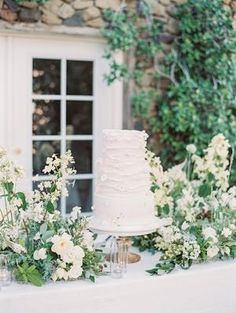 This elegant all-white cake is too sweet to handle! We love the abundant greenery decor bringing this cake table to life🌿 📸: Wedding Cake Fresh Flowers, White Wedding Flowers, Elegant Wedding Cakes, Wedding Cake Designs, Floral Wedding, Greenery Decor, All White Wedding, Wedding Cake Inspiration, Wedding Ideas
