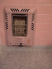 Pink tiled bathroom wall with electric heater