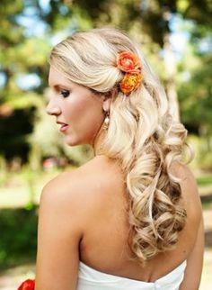 Bride's down wedding hairstyle with orange flowers