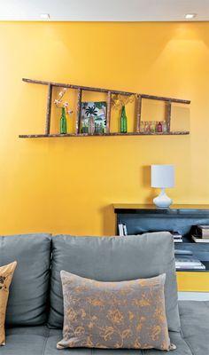 Essa escada, na parede amarela e com os objetos dentro, ficou linda!