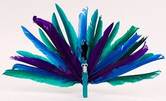 Step 1. Gather your supplies. Step 2.   Paint a wood clothespin with the turquoise jewel tone paint. Set aside to dry. Step 3. Fold a cupcake liner in half and begin gluing green feathers on to it. Step 4. After it is covered in green feathers, add a few blue and purple feathers as shown. Set … Continued