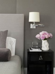 Gray bedroom with gray walls, gray linen headboard, gray velvet bolster pillow, glossy black nightstand and polished nickel wing-arm sconce. Black And Grey Bedroom, Gray Bedroom Walls, Grey Walls, Home Bedroom, Girls Bedroom, Gray Rooms, Master Bedroom, Bedroom Ideas, Bedroom Office