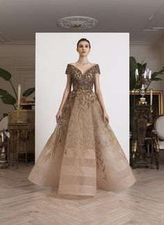 AZZI & OSTA: Off-shoulder, antique gold gown in tulle; hand-sequined bust, thread embroidery skirt with goldwork waist