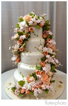 Sylvia Weinstock White wedding cake with handmade flowers. Peach and green accents.