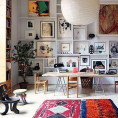 sala de jantar diferente, parede decorada com quadros dentro da estante. Tapete colorido