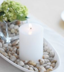 A plain white pillar candle on a small platter covered in stones with a single bloom in a square vase in the center. It would take you about as long to create it as it did for you to read how to do it. A hydrangea was used but you can use any other large bloom flower.