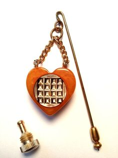 VINTAGE BUTTERSCOTCH BAKELITE HEART SHAPED PERFUME BOTTLE PIN/BROOCH! This fantastic vintage collectible bakelite piece is multi functional. Not only is it a great stick pin but a perfume bottle as well. This butterscotch colored heart shaped bakelite perfume bottle hangs from 2 gold colored chains and is attached to a stick pin. The cover screws off and the front is decorated with a detailed grey mother of pearl round disc. In great condition!