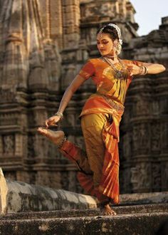The pinner said this may be Odissi dance, it certainly doesn't look like anything in Bharatnatyam but I LOVE the background, the whole scene is amazing... I would love to do a photoshoot at a temple