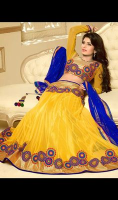 Make a perfect look to your attire by donning this gold color embroidered net lehenga choli. This attractive choli is showing some superb embroidery done with resham and stones work. #TraditionalFancyLehengaCholi