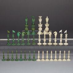 "ANGLO-INDIAN TURNED AND CARVED IVORY CHESS SET, KASHMIR, EARLY 19TH CENTURY one side stained green, each piece finely carved all over with foliate decoration, the kings and queen pierce carved with turreted waists, bishops with pierced miters, knights with horse heads, rooks as turrets with flags, height 4.75"" - 12.1 cm"