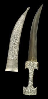 AN OTTOMAN DAGGER AND SHEATH TURKEY, CIRCA 1800 The double-edged curving watered steel blade with pronounced medial ridge and small floral and calligraphic cartouche at the forte, the waisted cylindrical hilt decorated in silver repoussé with a dense floral design, the sheath similarly decorated with panels of floral decoration between silver-wire and rope-like bands, with dragon head terminal, each of the elements with assay mark, remains of gilding 20¾in. (52.5cm.) long