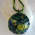 Polymer clay domed necklace in blues, yellow and green on 18' ball chain     Domestic shipping included, international customers please ask for shipping rates. Click Inselly link in bio or message me if interested.