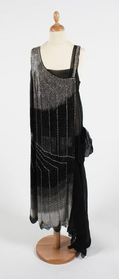 A black and silver beaded 1920s dress with tonal white, gray, and silver-to-black striped beadwork. Asymmetrical hip and shoulder design, on fine black silk chiffon crepe.