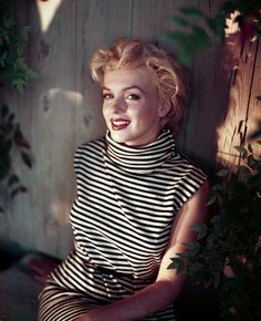 Marilyn Monroe looking radiant in red lipstick and a black & white striped turtleneck dress.  At home in Palm Springs.