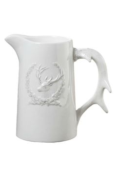 """Rustic elegance adorns your table and/or bar when using this beautiful crested Antler pitcher. The front of this lovely pitcher is dressed with a laurel crest and a buck head. And to complete this special piece, the handle is an antler.    Measures: 7"""" H x 4"""" diameter x 7"""" W   Crested Antler Pitcher by The Purple Porch. Home & Gifts - Home Decor - Dining - Serveware Tennessee"""