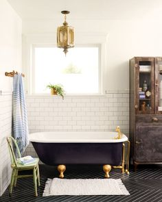 1920s claw-foot tub ($200) that Coley found on Craigslist. She had the inside resurfaced for $125, painted the outside black, and added polished brass fixtures. With its classic design and modern updates, the tub inspired the room's old-meets-new mix. Black porcelain floor tile, laid in a herringbone pattern, adds an unexpected edge. antique Moroccan lantern, and a storage cabinet salvaged from an aircraft carrier offset the sleek surfaces with a little patina.   - CountryLiving.com