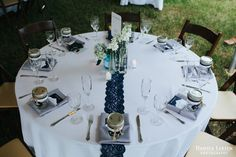 Outdoor backyard wedding reception. 8 foot round reception table, navy blue lace table runner, bud vase centerpiece, mason jar, blue hydrangea, white stock, lavender flowers. Photography: www.danicalarsen.com