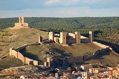 """CASTLES OF SPAIN - Castle of Molina de Aragón, Castile-La Mancha, Spain. It is located on a hill commanding the surrounding valley, and is formed by an external line of walls with four gates and numerous towers. It originated as a Moorish fortress (10th-11th century), built over a pre-existing Celtiberian castle. The fortress was used as residence of the lords of the moorish """"Taifa"""" of Molina. In 1129 it was conquered from the Moors by Alfonso I of Aragon."""