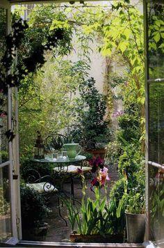 coin repas en plein air aménagé avec un mobilier en fer forgé et plongé dans la végétation luxuriante