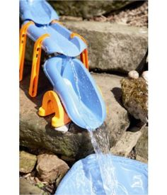 HABA outdoor toy - Starter Set with Water Seesaw set up on rocks and dumping into a water pond.