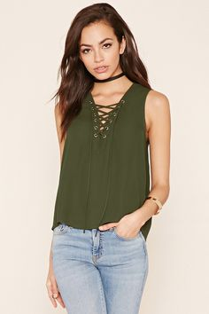 A chiffon top featuring a self-tie lace-up front, sleeveless cut, and a boxy silhouette.