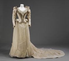 Wedding dress and shoes | Stern Bros 1890 Heavy cream corded silk wedding dress and trained skirt, bodice with accentuated waist and dramatically flared peplum, shirred leg o'mutton sleeves. Embroidered with pearls, pastes and gathered silk lisse (crêpe chiffon). Shoes of white satin embroidered with bronze and crystal, silk stockings.