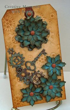 Steampunk tag created with Globecraft Piccolo embossing enamel and book board shapes.  Flowers are from Cheery Lynn Designs