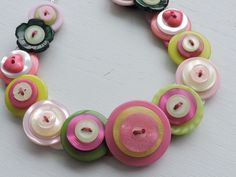 A pretty button necklace which I've made with assorted shades of pink, green and cream buttons. Layered, stacked, threaded and knotted and finished with little Aurora Borealis beads which sit comfortably around the back of the neck and a silver plated toggle clasp.   eBay!