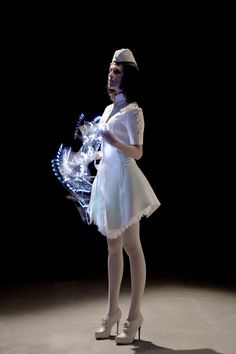 Vega Wang's Bioluminescent Couture artfully balances fashion with tech by creating breathtaking luminescent patterns from custom EL panels glowing from inside structured white clothing.