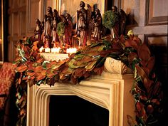 A set of 19th-century hand-carved angel figurines bring drama to this fireplace mantel. Delicate, juniper wreathes hang from the angels for another layer of texture, and votives give a soft glow. (Photo: Liesa Cole and Ann Stratton)