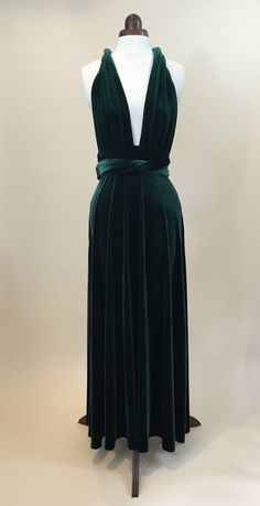 Beautiful infinity dress made in a rich bottle green velvet.  This versatile infinity dress can be worn in more than fifteen different ways by varying the wrapping of the two front vertical bands, with a number of options shown in the photos. It can thus be conservative or daring, and brings glamour to a variety of formal occasions such as balls, proms and dinners, as well as being a popular choice for bridesmaids. It is made with a soft stretch velvet which looks and feels very luxurious…
