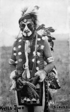 Standing portrait of a Native American (Brulé Sioux) man, identified as Kills Two, a Sioux medicine man. He is decoratively outfitted in leggings, a breech cloth, a hide vest with metallic disks, face paint, head band, and arm and wrist bands. Photo between 1880-1910, no photographer credit