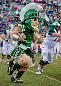 Sparty taking a snap at the spring football game.