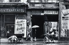"""Rue de Belleville, entrée de l'ancien passage Kuszner Photo de Claude Dityvon 1967  Ce passage, situé entre les n° 15 et 17 de la rue de Belleville, menait à la rue Rébéval. Au n°17, s'élevait un magasin qui fut renommé entre 1872 et 1962, la """"Halle aux Chapeaux"""", dont la publicité disait qu'il s'agissait du plus vaste entrepôt de chapellerie de la capitale... On n'en connait peu de photos (Willy Ronis et François-Xavier Bouchart, notamment). Comme beaucoup d'endroits à Belleville, il avait…"""