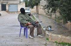 Shotgun & tea, a syrian rebel guards an alley at Rastan area in Homs province