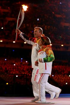 Vladislav Tretyak (L) carries the Olympic torch with Irina Rodina during the Opening Ceremony of the Sochi 2014 Winter Olympics at Fisht Oly...