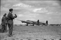 An Avro Lancaster B Mark I of No. 83 Squadron RAF is signalled off on the third 'Thousand Bomber' raid, an attack on Bremen, Germany from Scampton, Lincolnshire. The Wing Commander (Flying) gives a green light for take off with his Aldis lamp.