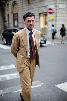 Beige suit, light blue shirt, brown knit tie