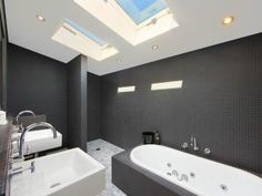 Designer bathroom with skylights and dual vanities